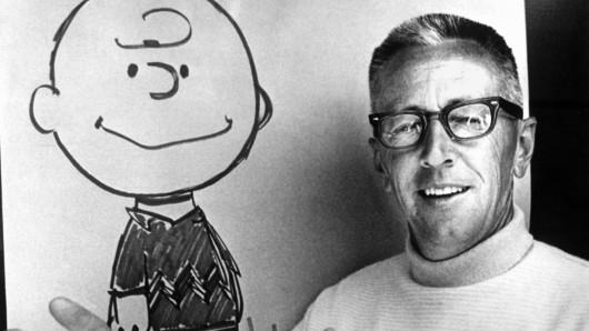 US-Comic-Zeichner und Erfinder der Peanuts, Charles M. Schulz, vor einem Blatt mit der gezeichneten Figur des Charlie Brown