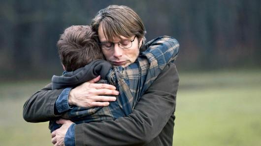Marcus (Lasse Fogelstrøm, li.) hält zu seinem unschuldigen Vater (Mads Mikkelsen, re.), der Opfer einer Verleumdung wird.