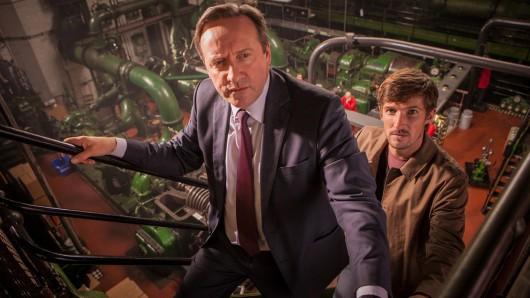 Barnaby (Neil Dudgeon, l.) und Nelson (Gwilym Lee, r.) durchsuchen die alte Keksfabrik nach Hinweisen auf den Mord.