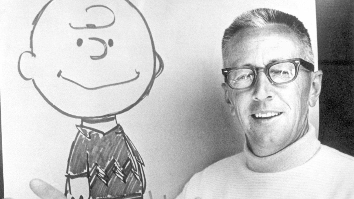 """US-Comic-Zeichner und Erfinder der """"Peanuts"""", Charles M. Schulz, vor einem Blatt mit der gezeichneten Figur des Charlie Brown"""