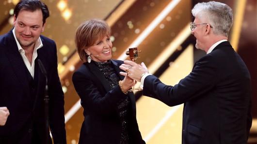 Schauspielerin Ulrike Kriener überreicht den Preis in der Kategorie Bester deutscher Fernsehfilm an die Gewinner, das Team von der Komödie Jürgen - Heute wird gelebt. (u.a. Charly Hübner (l), Heinz Strunk).