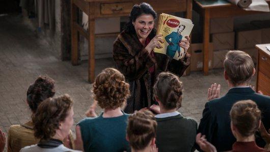 In ihrer neuen Paraderolle als Aenne Burda - Die Wirtschaftswunderfrau präsentiert Katharina Wackernagel ihrer Filmbelegschaft 1950 die erste Ausgabe von Burda Moden.