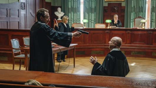 Anwalt Thomas Peters (Thorsten Merten) erschießt im laufenden Prozess einen Richter. Kurz vor der Tat schaut er auf die Uhr und wartet die volle Stunde ab.