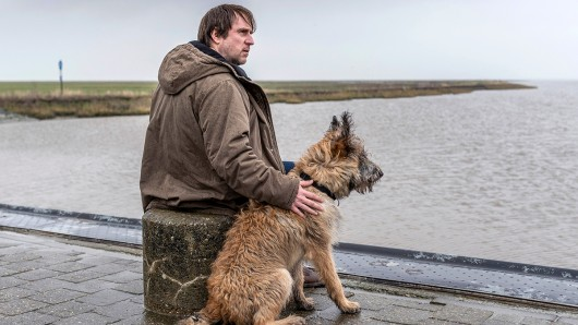 Sörensen (Bjarne Mädel) mit Hund Cord vor dem nordfriesischen Wattenmeer.