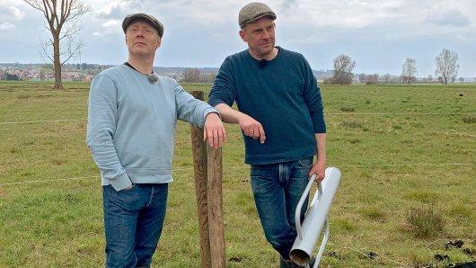 Von links: Simon Schwarz und Sebastian Bezzel lehnen an einem Weidezaun.