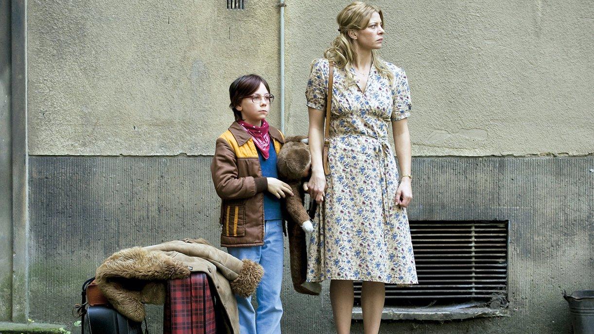 Nelly (Jördis Triebel) und ihr Sohn Alexej (Tristan Göbel) warten samt Gepäck auf die Abholung nahe der Grenze.