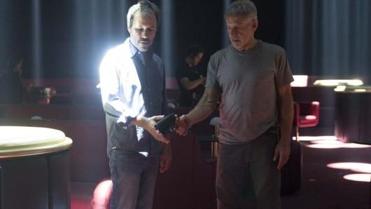 Am Set von Blade Runner 2049: Franchise-Rückkehrer Harrison Ford zeigt Regisseur Denis Villeneuve, wie man in der Zukunft mit Waffen hantiert