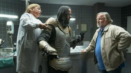 Thiel (Axel Prahl, r.) hört, was Boerne (Jan Josef Liefers) zu sagen hat, während ihm Silke Haller (ChrisTine Urspruch) in der Rechtsmedizin dabei hilft, die Ritterrüstung anzulegen.